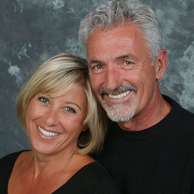 Man and woman with healthy smiles after dental implant tooth replacement
