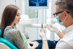 Dentist showing woman dental implant model