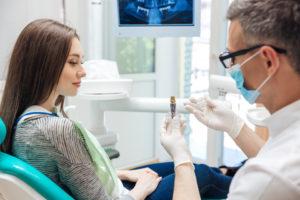 Dentist showing woman dental implant model