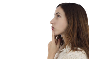 woman with finger to mouth pondering