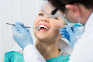 woman smiling while receiving dental checkup