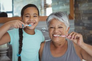 parent and child brushing their teeth together