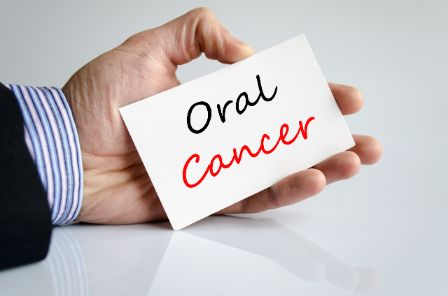 Someone holding a card that reads, Oral Cancer