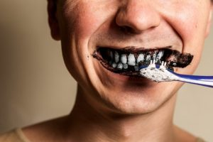 person brushing their teeth with activated charcoal