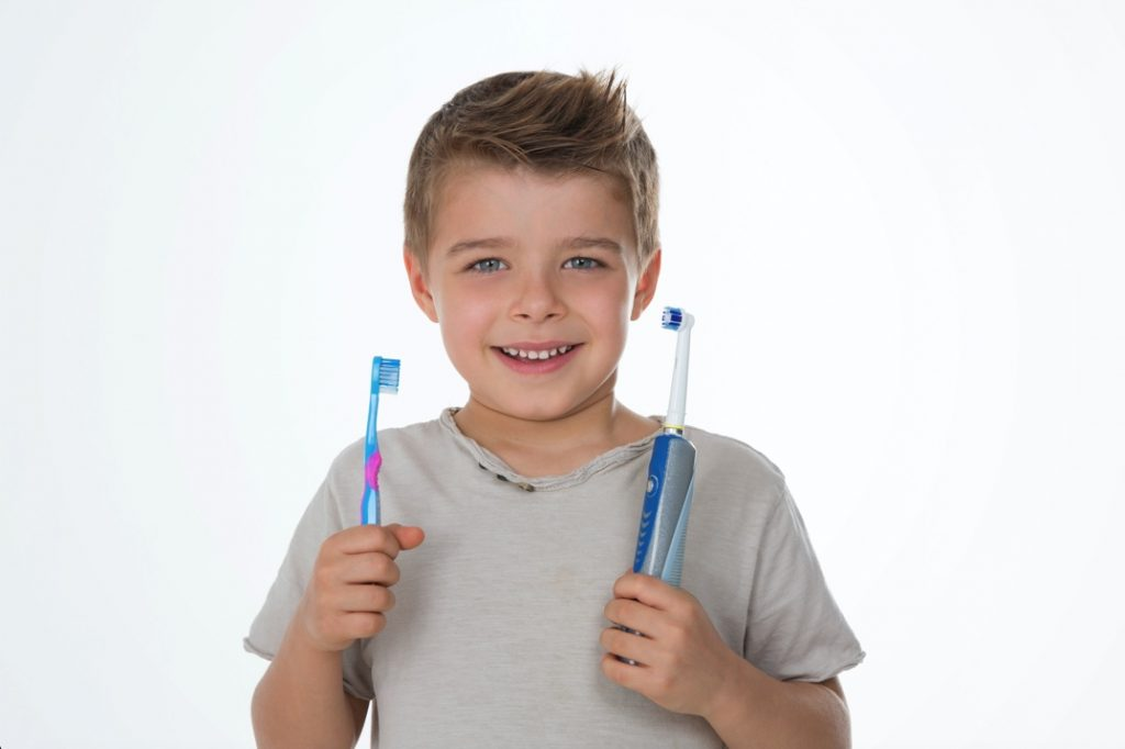 Boy holding manual and electric toothbrush