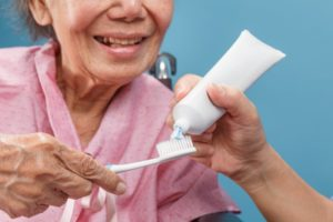 Older woman holding a toothbrush as someone puts toothpaste on it