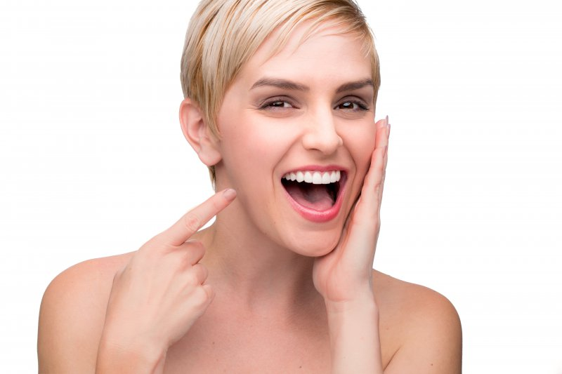 Woman pointing at her new smile from a cosmetic dentist.